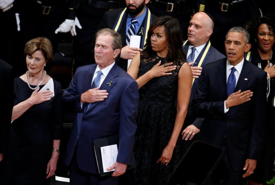 Former first lady Laura Bush, former U.S. President George W. Bush, first lady Michelle Obama and President Barack Obama hold their hands on their hearts as they sing the national anthem July 12 at a memorial service held in honor of police officers killed and wounded in shootings in Dallas. CNS photo/Carlo Allegri, Reuters
