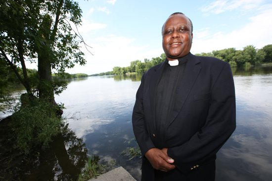 "Father Robert Mutui of the Diocese of Kitui, Kenya, enjoys seeing Minnesota's copious amounts of water, including the Mississippi River, which runs less than a mile from St. John the Baptist in Dayton. He said he wishes he could use ""a giant pipe"" to take some of the water from the river back to his country, which often experiences severe drought. Dave Hrbacek/ The Catholic Spirit"