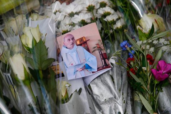 A photo of slain Father Jacques Hamel is seen among flowers at a makeshift memorial in Saint-Etienne-du-Rouvray, near Rouen, France, July 27. CNS photo/Ian Langsdon, EPA