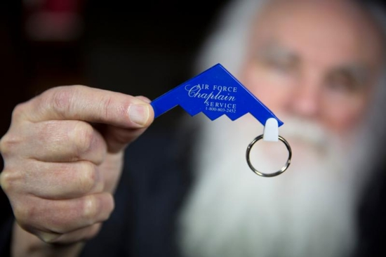Melkite Father Emmanuel Charles McCarthy holds up an old keychain in the shape of a fighter plane representing the Air Force Chaplain Service, which he says creates an image that is not fit for any Catholic priest. This photo was taken at Father McCarthy's Brockton, Mass., home April 4. CNS photo/Chaz Muth
