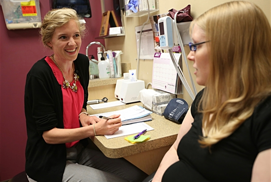 Sarah Slattery, left, physician assistant at AALFA Family Clinic in White Bear Lake, talks with patient Becca Kempenich, who was there with her husband, Dan, and newborn son, Xander. Dave Hrbacek/The Catholic Spirit