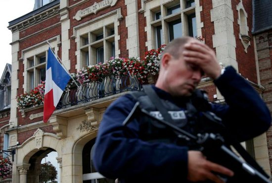 A policeman reacts as he secures a position in front of city hall after two assailants killed 84-year-old Father Jacques Hamel and took five people hostage during a weekday morning Mass at the church in Saint-Etienne-du-Rouvray, France, near Rouen July 26. CNS photo/Pascal Rossignol/Reuters