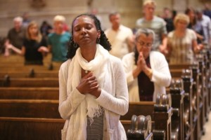Eleni Demissie of the Cathedral of St. Paul prays during Mass for the Preservation of Peace and Justice at the Cathedral of St. Paul July 8. Dave Hrbacek/The Catholic Spirit