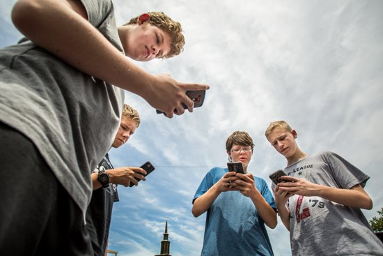 Alec Richardson, Brennan Moore, Adam Salman and Blake Koelz hunt Pokemon stops July 14 around the grounds of Assumption Church in St. Louis. CNS photo/Lisa Johnston, St. Louis Review