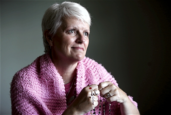 Rhonda Zweber of St. Michael in Prior Lake uses a rosary and prayer shawl in her own battle with cancer and to deepen the faith that inspires her to serve others with the disease. Dave Hrbacek/The Catholic Spirit