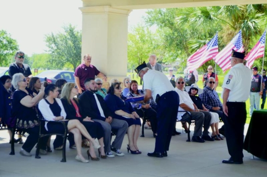 American Legion Post 93 Cmdr. Rudy Flores presents the burial flag to the family of Army veteran Jacky Eugene Gonzalez during his June 22 funeral at the Rio Grande Valley State Veterans Cemetery in Mission, Texas. Flores and other U.S. military veterans, perform these solemn duties several times a week, usually at the veterans cemetery, but they will go wherever they are needed. CNS photo/Rose Ybarra, The Valley Catholic