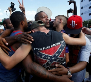 "African-American and white men embrace after taking part in a prayer circle July 10 following a Black Lives Matter protest in Dallas. Theologians and justice advocates have called upon the church to better address racism as a life issue and see it as an ""intrinsic evil."" CNS photo/Carlo Allegri, Reuters"