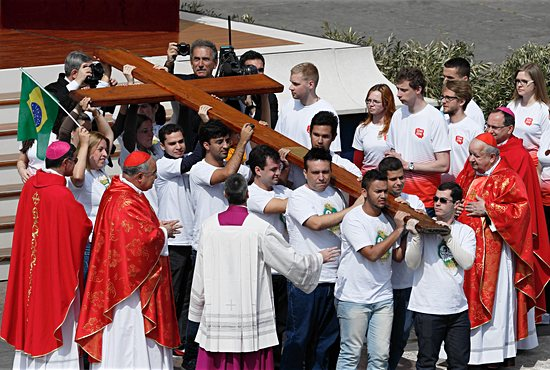 Young people from Brazil, left, pass on the World Youth Day cross to youths from Poland, right, at the conclusion of Pope Francis' celebration of Palm Sunday Mass in St. Peter's Square at the Vatican April 13, 2014. The next international Catholic youth gathering will be July 25-31 in Krakow, Poland. CNS/Paul Haring