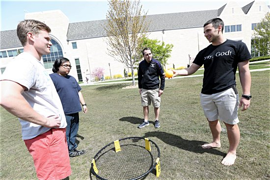 St. Paul Outreach Mission Leader Austin Riordan, right, plays Spikeball with University of St. Thomas students Kuba Bursey, left, Richard Adrian and Robert Klemm.
