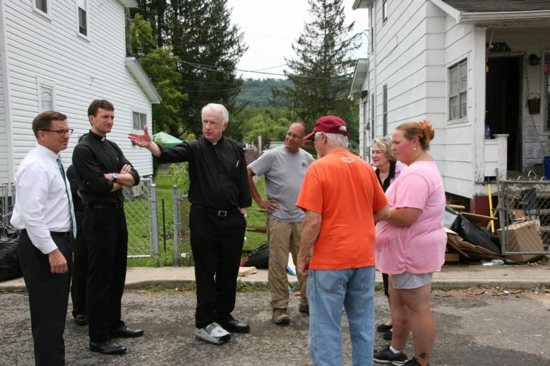 Bishop Michael J. Bransfield of Wheeling-Charleston, W.Va., tours a neighborhood in Rainelle, W.Va., July 25 that was ravaged by flood waters in June. CNS photo/Tim Bishop, Catholic Spirit