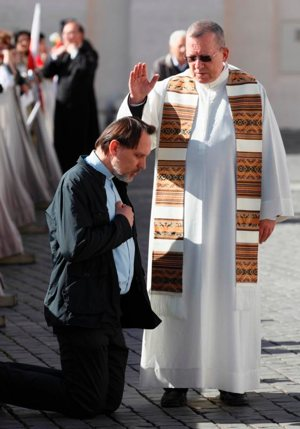 A priest hears a confession in St. Peter's Square at the Vatican, April 28, 2014. God's mercy is highlighted in the sacrament of reconciliation, Pope Francis said in a message to bishops, priests and church workers attending Italy's annual week of liturgical studies. CNS photo/Paul Haring