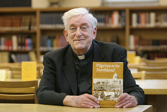 "Father Marvin O'Connell, a priest of the Archdiocese of St. Paul and Minneapolis and historian, holds his book ""Pilgrims to the Northland: The Archdiocese of St. Paul, 1840-1962"" in this 2009 file photo. Dave Hrbacek/The Catholic Spirit"