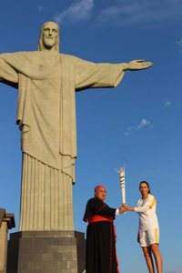 Cardinal Orani Tempesta of Rio de Janeiro and former Brazilian volleyball player Isabel Barroso hold the Olympic torch in front of the Christ the Redeemer statue in Rio de Janeiro Aug. 5. CNS photo/Lise Alves