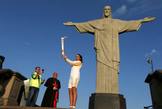 Former Brazilian volleyball player Isabel Barroso holds the Olympic torch Aug. 5 next to the Christ the Redeemer statue as Rio de Janeiro Mayor Eduardo Paes and Cardinal Orani Tempesta look on. CNS photo/Pilar Olivares, Reuters