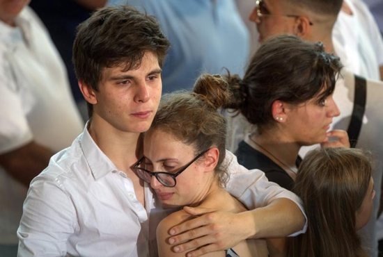 "A man comforts a woman after an Aug. 27 mass funeral for earthquake victims inside a gym in Ascoli Piceno, Italy. Pope Francis said he would visit survivors of the Aug. 24 quake ""as soon as possible."" The 6.2 earthquake left hundreds dead and thousands homeless. CNS photo/Adamo Di Loreto, Reuters"