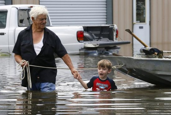Richard Rossi and his 4-year-old great-grandson Justice wade through water Aug. 15 after their home flooded in St. Amant, La. CNS photo/Jonathan Bachman, Reuters