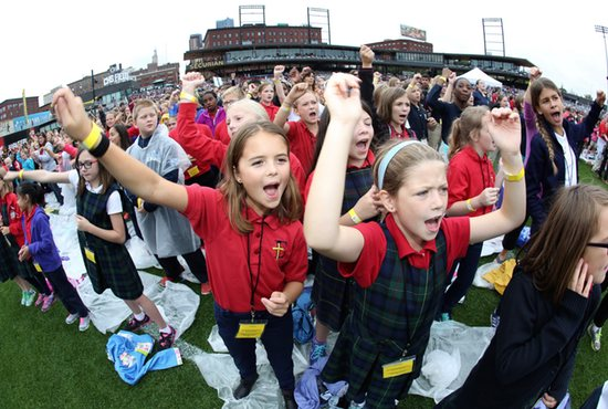 From left, fourth-graders Gabby Noren and Isabel Scalia of Epiphany School in Coon Rapids cheer during music played by local band Sonar at the Mass of the Holy Spirit Sept. 22 at CHS Field in St. Paul. Catholic elementary students in grades four through eight came for the Mass, celebrated by Archbishop Bernard Hebda and Bishop Andrew Cozzens. Dave Hrbacek/The Catholic Spirit