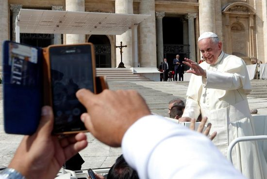 A pilgrim takes a cell phone picture as Pope Francis waves at the end of his weekly audience Sept. 28 in St. Peter's Square at the Vatican. CNS photo/Remo Casilli, Reuters