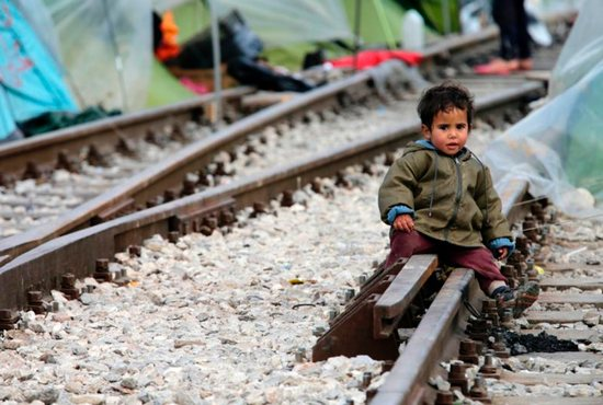 A child sits on railroad tracks near a makeshift camp for migrants in late March at the Greek-Macedonian border near the village of in Idomeni, Greece. Children are the most vulnerable and hardest hit among the world's migrants and require special protection, Pope Francis said. CNS photo/Armando Babani, EPA