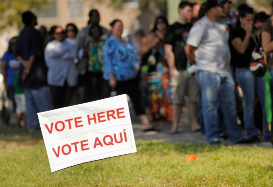 A sign in English and Spanish is seen as people wait to vote in 2012 outside a polling place in Kissimmee, Fla. A Pew Research Center poll released Oct. 10 shows Hispanic Americans give nearly a 5-1 edge to Democrats over Republicans as the party they feel is more concerned for them. CNS photo/Scott A. Miller, Reuters
