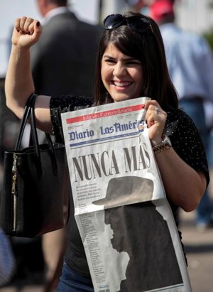 "A woman gestures while holding a newspaper with a image of Cuban revolutionary leader Fidel Castro that reads in Spanish, ""Never Again,"" a day after the announcement of the death of Castro, in the Little Havana district of Miami Nov. 27. Castro, who seized power in a 1959 revolution and governed Cuba until 2006, died Nov. 25 at the age of 90. CNS photo/Javier Galeano, Reuters"