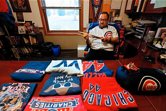 Father John W. Clemens, pastor of Our Lady of Hope Church in Rosemont, Ill., poses for a photo Oct. 27 near his jersey signed by Chicago Cubs legend Ernie Banks. Karen Callaway/Catholic New World