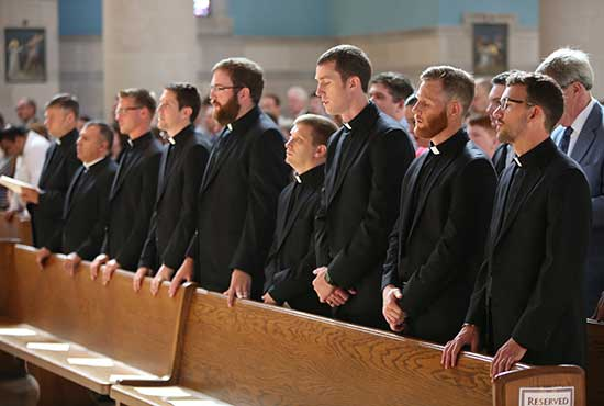 Nine Jesuit novices prepare to make their first profession of vows at St. Thomas More in St. Paul Aug. 13 ­­— from left, Michael Bartlett, José Camacho, Pierce Gibson, David Inczauskis, James Kennedy, James McGivney, Jack McLinden, Thomas O'Donnell and Christopher Williams. Dave Hrbacek/The Catholic Spirit