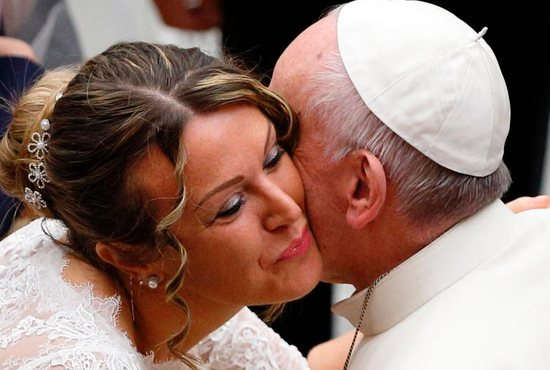 A newly married woman wearing her wedding dress kisses Pope Francis during his general audience in Paul VI hall at the Vatican Nov. 30. CNS photo/Paul Haring