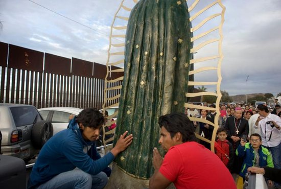 A statue of the Our Lady of Guadalupe is carried in a truck during a procession to the U.S.-Mexico border fence in Tijuana, Mexico, where Mass was celebrated. The Mass and a procession with a statue of Our Lady of Guadalupe were a call to remember and pray for migrants and were led by Archbishop Francisco Moreno Barron of Tijuana. CNS photo/David Maung