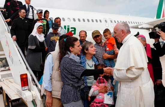 Pope Francis greets Syrian refugees he brought to Rome from the Greek island of Lesbos, at Ciampino airport in Rome April 16, 2016. The pope concluded his one-day visit to Greece by bringing 12 Syrian refugees to Italy aboard his flight. CNS photo/Paul Haring