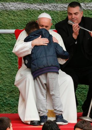 Pope Francis embraces Emanuele, a boy whose father died