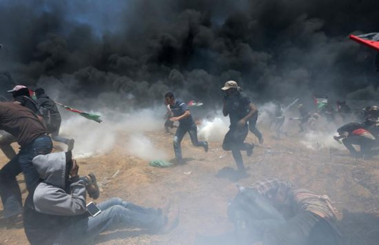 Palestinians run for cover from Israeli fire and tear gas at the Israel-Gaza border during a protest against the U.S. embassy move to Jerusalem