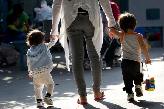 A woman walks with children at a shelter for migrant women and children in Tijuana, Mexico