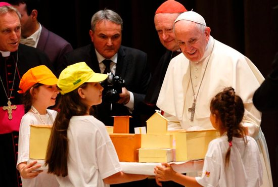 "Pope Francis accepts a gift during an audience with children participating in the ""Train of Children"" at the Vatican"