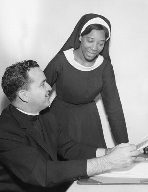 An African-American woman religious consults with a priest in an undated photo at the National Black Sisters' Conference headquarters in Washington.