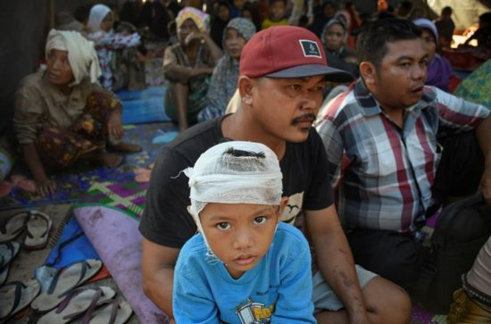 A young earthquake survivor sits with his family inside a makeshift tent July 30 on the island of Lombok in Indonesia.