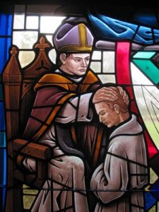 A stained-glass window depicts the sacrament of holy orders in St. James Cathedral in Orlando, Fla. Priests internationally continue to play diverse and integral roles in marriage preparation.