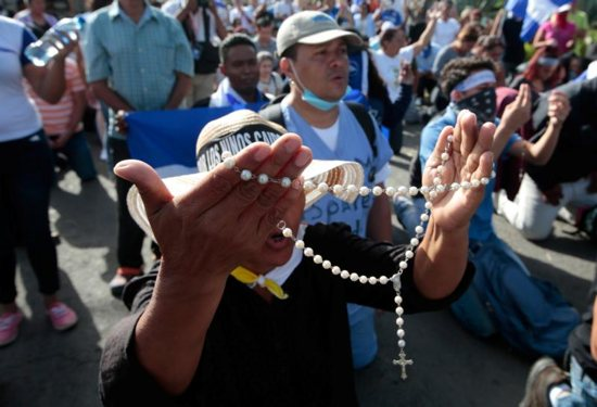 People pray in front of police who block the entrance to Divine Mercy Catholic Church July 14, where students from the National Autonomous University of Nicaragua sought refuge in Managua.