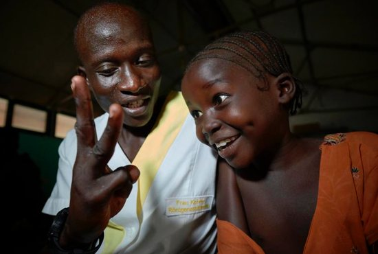 Nurse Isaac Langurry interacts with a young girl wrestling with blindness in late April in the pediatric ward of the Mother of Mercy Hospital in Gidel, a village in the Nuba Mountains of Sudan.