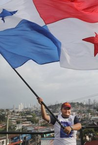 With Panama City as the backdrop, a young man waves the flag of Panama following a prayer vigil for young people in late April at the Church of Christ the Redeemer outside Panama City.