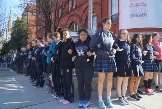Presentation Academy students stand arm in arm on the sidewalk in downtown Louisville, Ky., after walking out of class March 14 to call attention to gun violence.