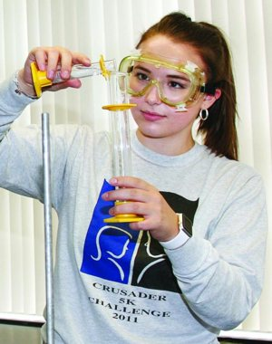 Macie Westrick, a senior at Parkersburg Catholic High School in Parkersburg, W.Va., conducts a science experiment at the school Oct. 7, 2017.