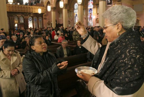 An extraordinary minister of the holy Eucharist distributes Communion during Mass at Transfiguration Church in the Williamsburg section of Brooklyn, N.Y.