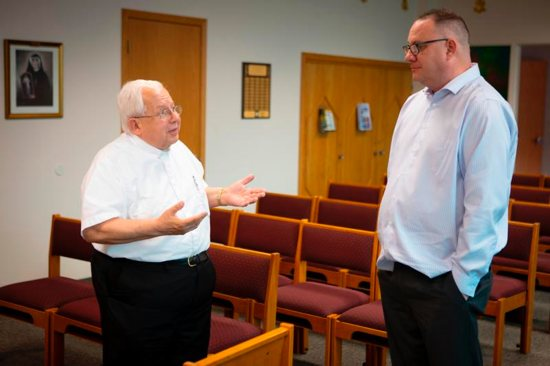 Pittsburgh resident Jim VanSickle, who told a Pennsylvania grand jury that he was molested by a priest when he was a teenager, speaks with Father Raymond Gramata, pastor at his boyhood parish