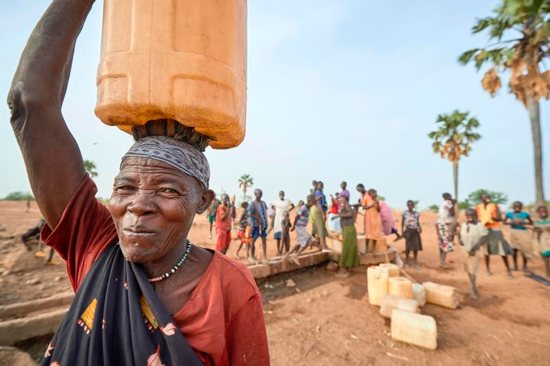 A woman carries water from a well in Lugi, a village in the Nuba Mountains of Sudan.
