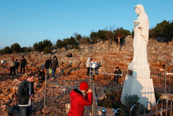 Pilgrims pray in front of a statue of Mary on Apparition Hill in Medjugorje, Bosnia-Herzegovina, in 2011