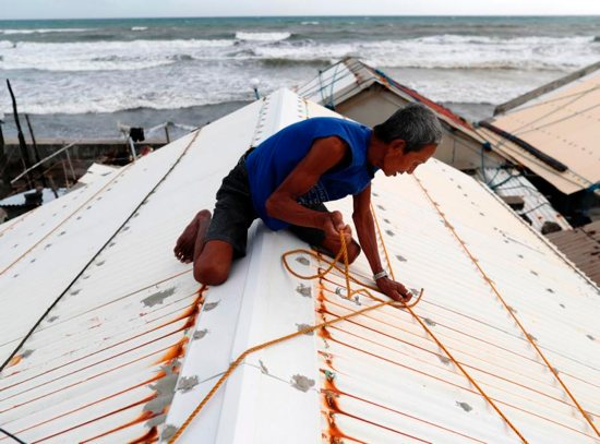 A man secures the roof of his home Sept. 14 in preparation for super Typhoon Mangkhut in the village of Aparri, Philippines.