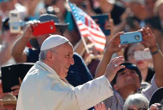 The U.S. flag is seen as Pope Francis greets the crowd during his general audience in St. Peter's Square at the Vatican Sept.
