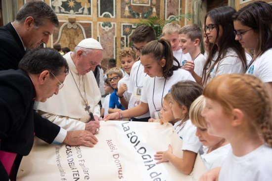 "Pope Francis signs a banner Sept. 13 during a meeting at the Vatican with people who were to take part in the conference, ""Pope Francis' Theology of Tenderness,"" in Assisi, Italy"