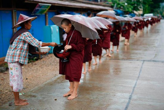 A woman offers food alms to Buddhist novices at Hpa-An town, Myanmar, Aug. 2. The U.S. International Commission on Religious Freedom singled out 28 countries for their repression of religious liberty in its annual report, issued Aug. 29.